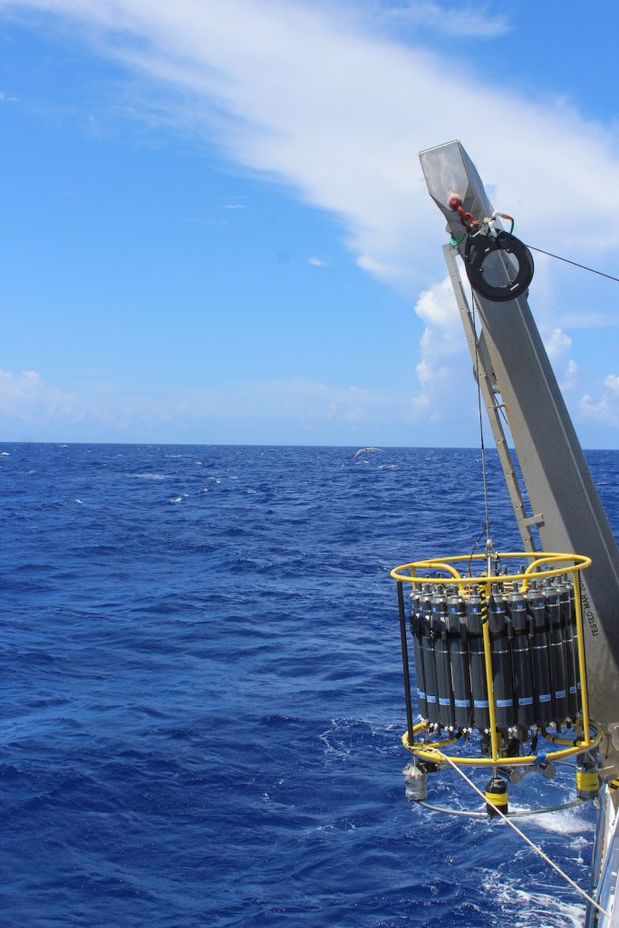 The CTD being carefully deployed off the starboard side of the boat. Two ropes held by technicians make sure the structure enters the water straight