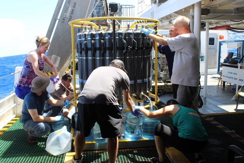 Scientists on the R.V. Atlantic Explorer surround the CTD, a structure holding their water samples to collect the water quickly.